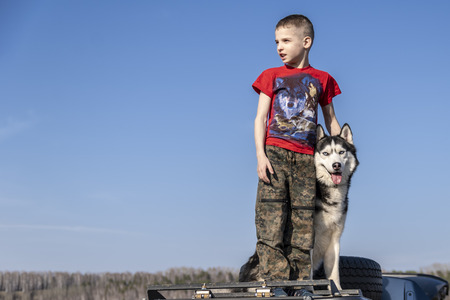 Boy hugged with love Siberian husky dog on blue color sky background. Family lifestyle. Friends together. Happy dog is smiling. Walk outside the city.