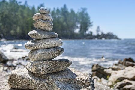 Pyramide de pierres, sculpture sur pierre, contre le ciel et l'eau. Pierres de cairn empilées dans la colline.