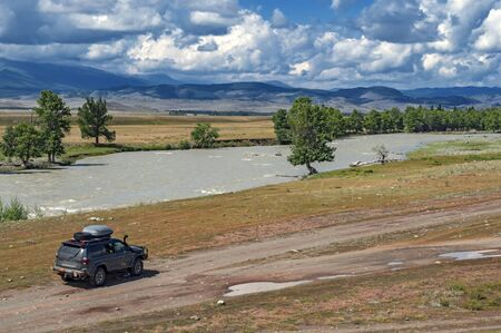 Mountain summer landscape. Steppe, river, tourist expedition car driving on a dirt road on the background of mountains and clouds.  Adventure travel, Mountain hill valley landscape. Zdjęcie Seryjne