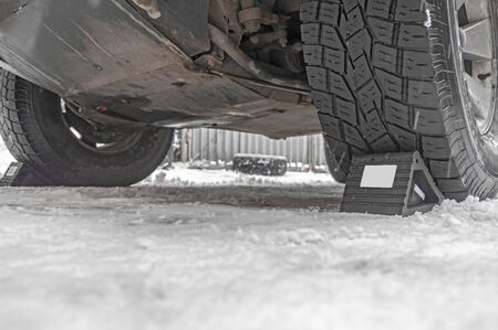 Wheel Chocks anti-skid. Prevent tires from rolling by set chock on front wheel on rough ground. Triangular anti-slip base. Stock Photo
