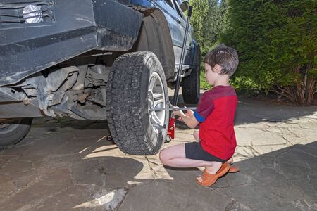 Boy in red t-shirt unscrews the nuts on the wheel of large off-road car. Child unscrews  nuts with cross wrench in the yard house. Sunny summer day. Standard-Bild
