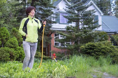 Woman watering plants in the garden. Work in the garden. Smiling gardener girl splashes water in the garden. Watering jet equipment.