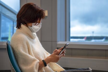 Girl in antiviral mask in the airport and looks at the screen of her smartphone. Side view. Copy space.