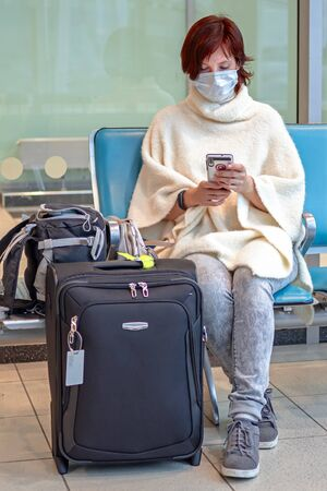 Girl in protective antiviral mask sits in the airport and looks at her smartphone. Woman with suitcases waiting for the flight in protected sanitary mask. Front view.