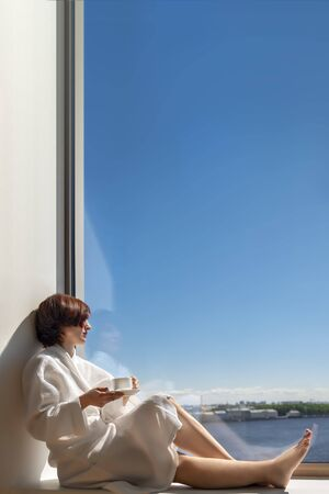Woman in white bathrobe enjoying sunny sea view next to big window with cup of coffee. Panoramic window with blue sky. Positive, enjoy, relaxation, rest. Copy sace. Side view.