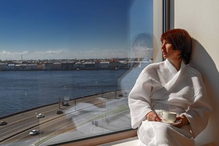 Beautiful middle age woman drinking tea sitting by the window. Middle-aged lady rests at large panoramic window. River and city landscape, sunny day with clear blue sky. Copy space.