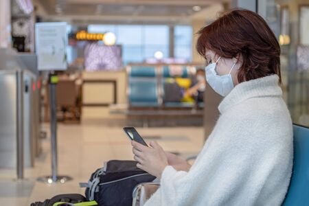 Girl in antiviral mask in the airport and looks at her smartphone. Side view, copy space Standard-Bild