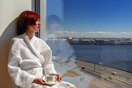 Middle aged woman in white bathrobe enjoying sunny river view next to big window with cup. Panoramic window with blue sky and urban landscape with river. Copy space. Standard-Bild