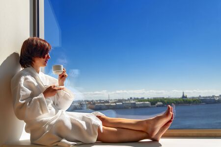 Woman in white bathrobe enjoying sunny river view next to big window with cup of coffee. Panoramic window with blue sky. Positive, enjoy, relaxation, rest. Copy sace. Side view. Standard-Bild