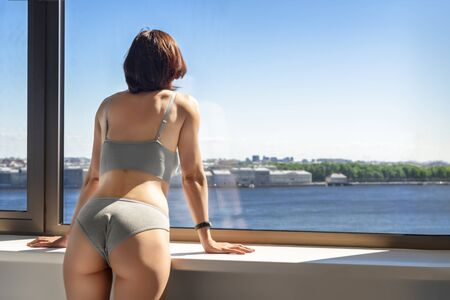 Girl in underwear looks out the panoramic window on blue sky in sunny day. Back view, slim athletic figure of a woman. Copy space.