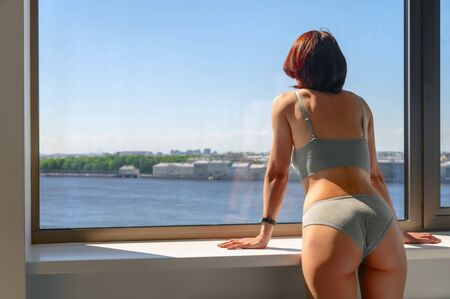 Girl in underwear looks out the window on blue sky in sunny day. Back view, slim athletic figure of woman. Copy space.