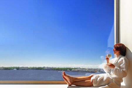 Middle aged woman in white bathrobe enjoying sunny river view next to large window with white cup. Panoramic window with blue sky and river. Copy space.