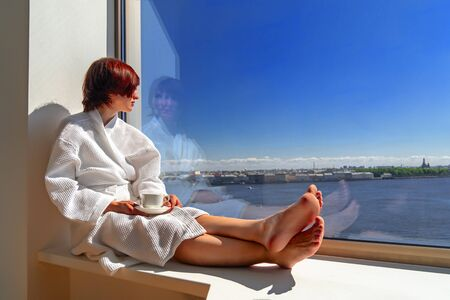 Woman in white bathrobe enjoying sunny sea view next to big window with cup of coffee. Panoramic window with blue sky. Positive, enjoy, relaxation, rest. Copy sace.