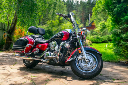 Moscow, July 09, 2020 - Motorcycle on the parking lot at the house. Background of the summer sunny garden in the backyard. Standard-Bild