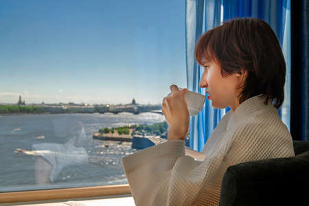 Woman drinks tea near large window in hotel. Woman looks at the landscape of  summer city with river. Portrait side view.
