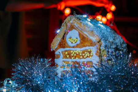 Gingerbread house with garland on dark background.