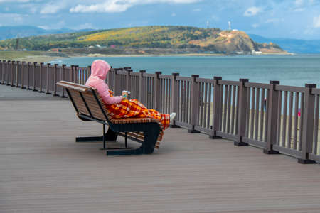 Woman, snuggled in sun lounger covered by plaid blanket. Cold autumn day on the beach.