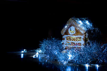 Gingerbread house with garland on black background. Copy space.