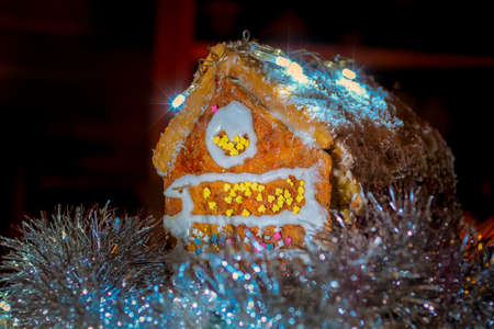Gingerbread family near snow-covered homemade gingerbread house with Christmas lights on dark background.
