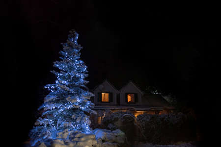 Christmas tree with garlands on the background of the house. Night Christmas holiday landscape. Cozy courtyard of the house in the snow. Standard-Bild