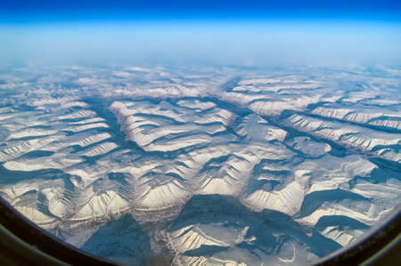 View from the plane porthole. Polar region, mountains in snow, sunny day. Arctic. Standard-Bild