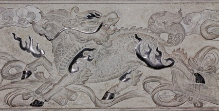 Dragon-headed unicorn or Chinese Unicorn Qilin  on a Chinese Temple wall, Qilin a dragon head with his wide body and wide  The surface is covered with scales  Tail-like oxtail  And a horse hoof  It is symbolic of healthy, good luck and happiness  photo