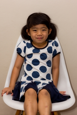 A little Asian girl on the chair Stock Photo - 16058094