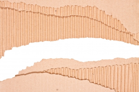 Hole ripped in corrugated cardboard on white background  with space for text or image photo