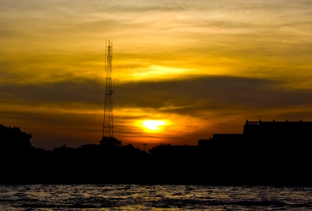 communication tower at sunset with cityscape Stock Photo