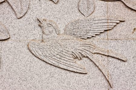 Bird carved on stone wall in chinese temple, Thailand  photo