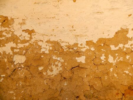 Old clay plaster, cracked on the wall. Deep cracks and beautiful texture