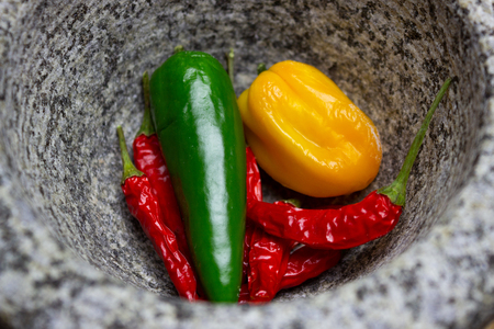 Red, green and yellow chilies in a mortar