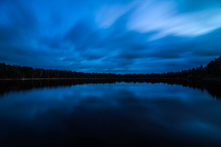 View of a peaceful lake and a beautiful sky. Long exposure with clouds Looking like fluids. Blue hour in the morning. Banco de Imagens