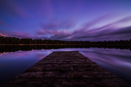 View of a peaceful lake with a boardwalk and a sky in the evening. Long exposure shot.