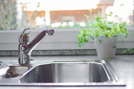 Clean chrome sink and a window with nice garden view in the background. Concept for a beautiful and modern kitchen. Marble countertop