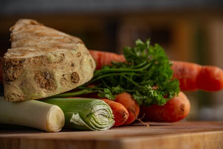 Raw vegetables on a wooden plate in the kitchen. Ingredients that come directly from the garden. Vegan cooking concept. Stockfoto