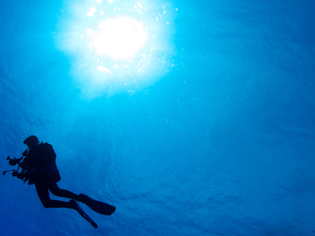 Silhouetted diver with blue water background and sun ball