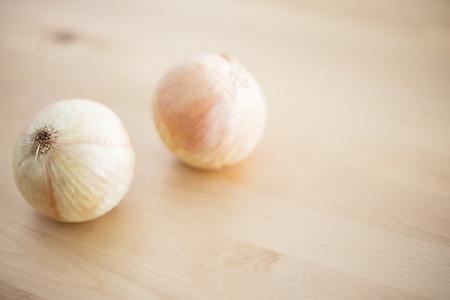 Raw onions on wood table Reklamní fotografie