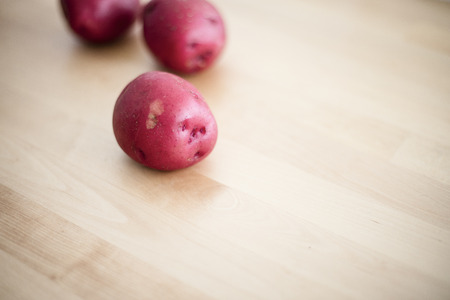 Raw red potatoes on wood table
