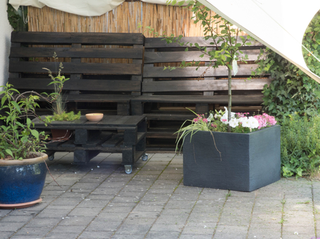 Pallet furniture under an awning on the house wall
