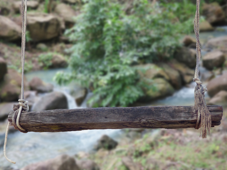 untouched: wooden bench with ropes front of blurred waterfall background 3d illustration