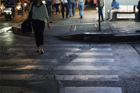 Crosswalk at night in the city with female business person walking