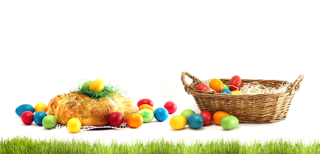 basket with easter eggs with challah yeast pastries bread plait isolated with blades of grass