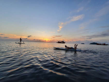 on a stand up paddle board, young man 34 years old, German, lies on a board on the ocean in Thailand, on the island Koh Tao at sunset