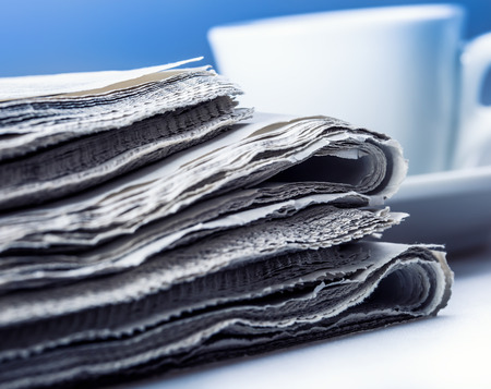 Several pieces of newspaper on a table with a cup of coffee in the background photo
