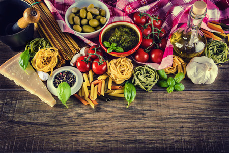 pasta: Italian and Mediterranean food ingredients on old wooden background.spaghetti olives basil cherry tomato pesto pasta garlic pepper olive oil and mortar. Stock Photo
