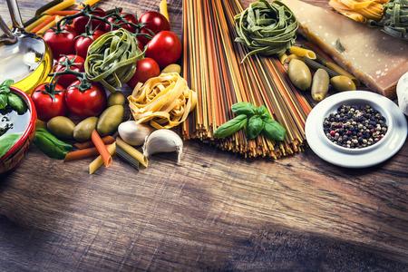 ajo: Ingredientes de la comida italiana y mediterr�nea en edad aceitunas background.spaghetti madera tomate albahaca cereza pasta al pesto de ajo pimienta aceite de oliva y el mortero.