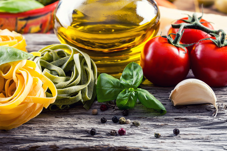 Italian and Mediterranean food ingredients on old wooden background.spaghetti olives basil cherry tomato pesto pasta garlic pepper olive oil and mortar. Standard-Bild