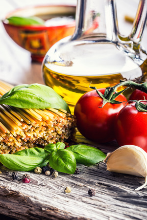 Italian and Mediterranean food ingredients on old wooden background.spaghetti olives basil pesto pasta garlic pepper olive oil and mortar. Standard-Bild