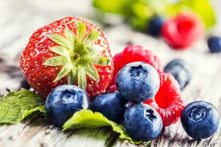 Bayas sobre fondo de madera o tabla. Arándanos, frambuesas, fresas, frutas del bosque. Jardinería, agricultura, cosecha y el concepto de bosque.